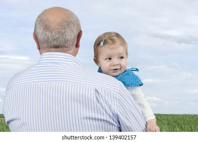 grandfather with granddaughter , outdoors in meadow