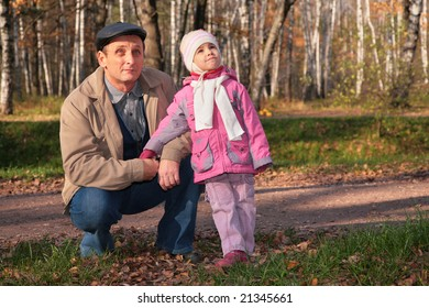 Grandfather with  granddaughter in park in autumn look upward