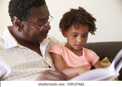 Grandfather And Granddaughter Reading Book At Home Together