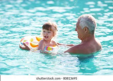 grandfather and granddaughter swimming in the pool
