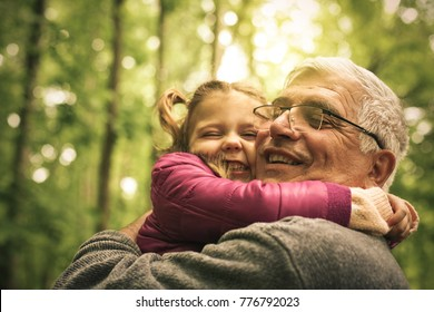 Grandfather and granddaughter talking in woods.
