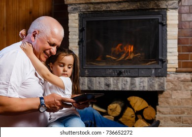 Grandfather and granddaughter using tablet of a house near the fireplace