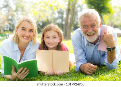Grandfather and grandmother of the elder family reading a book with granddaughter in the park.
