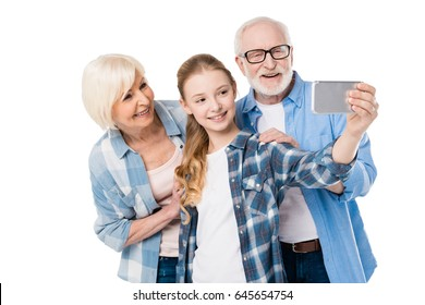 grandfather, grandmother and granddaughter taking selfie together isolated on white