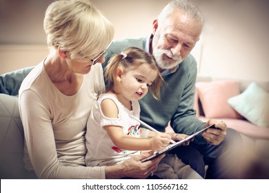 Grandfather and grandmother spending time and writing with granddaughter. Close up.