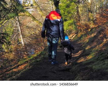 Grandfather and grandson.  Alyth, Blairgowrie, Scotland - February 15, 2019 Grandfather walks with his grandson at the escarpment at the Reekie Linn waterfall in Scotland.