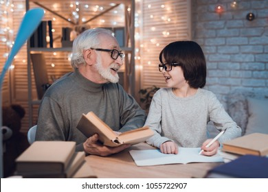 Grandfather and grandson are doing homework at table at night at home. Granddad is helping boy.