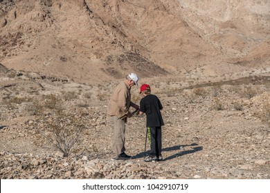 Grandfather and grandson exploring in the desert with mountains in the background