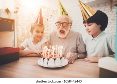 Grandfather, grandson and granddaughter at table at home. Grandpa is blowing candles on birthday cake.