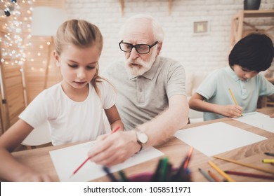 Grandfather, grandson and granddaughter at table at home. Children are drawing.
