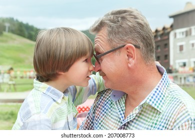 grandfather and grandson look at each other