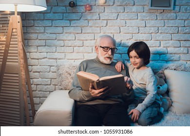 Grandfather and grandson on couch at night at home. Granddad is reading fairy tales book.
