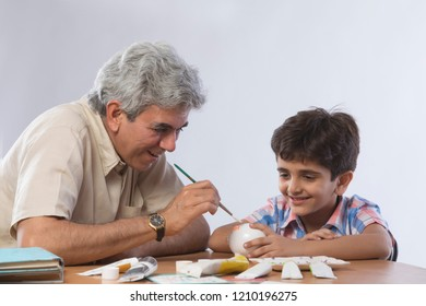 Grandfather and grandson painting piggy bank