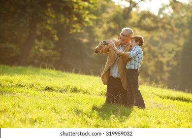 Grandfather and grandson photographing nature in park