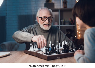 Grandfather and grandson are playing chess together at table at night at home.