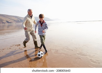 Grandfather And Grandson Playing Football On Winter Beach