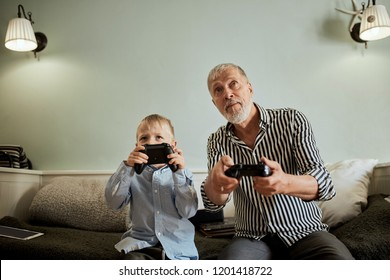 grandfather and grandson playing video game with joysticks in bed room while sitting on couch