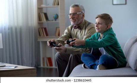 Grandfather and grandson playing video game with console, happy time together