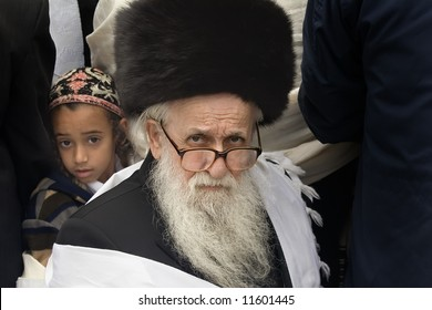 Grandfather and grandson pray in the wailing wall in Jerusalem.