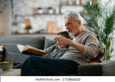 Grandfather and grandson reading a book. Grandpa and grandson enjoying at home.