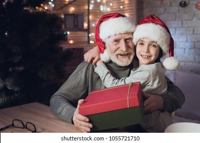Grandfather and grandson in Santa Claus's hats at table at night at home. Granddad is giving boy present.