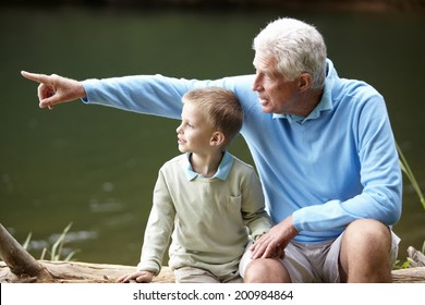 Grandfather and grandson sitting by lake