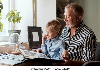 Grandfather and grandson sitting at couch and watch family album