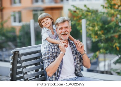 Grandfather and grandson walking in the park together in a sunny day. Grandson is playing with his grandfather at the park. Grandfather and grandson is looking to the camera.