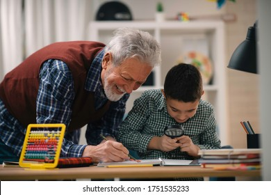 Grandfather and grandson working homework together. Grandpa and grandson enjoying at home.