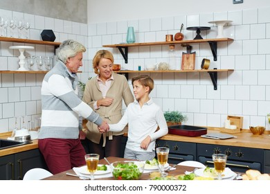 Grandfather handshaking with grandson in the kitchen with grandmother near by