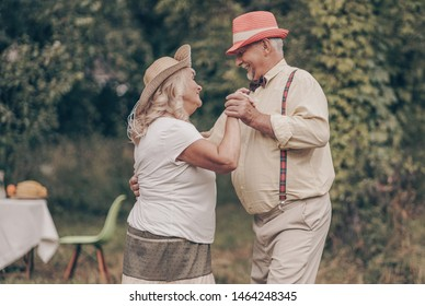 A grandfather with happy eyes looks grandmother in the eyes. Youth memories. The concept of a happy old age. Portrait of oldies who are dancing in the garden
