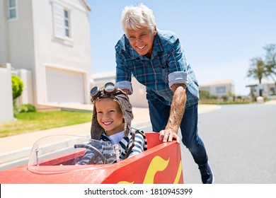Grandfather helping grandson ride on kid toy car outdoor. Senior man pushing child gokart while wearing pilot helmet on lane. Old granddad playing with grandchild riding toy race car on walkway.
