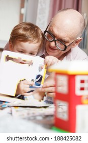 Grandfather helping  his little grandson to solve puzzle. Happy family time