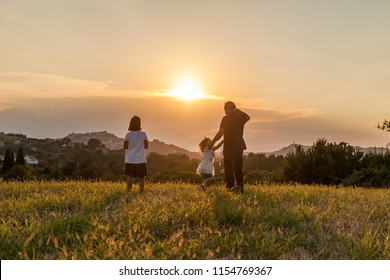 Grandfather and his children silhouette look to the horizon in the sunset light. Family and love icon