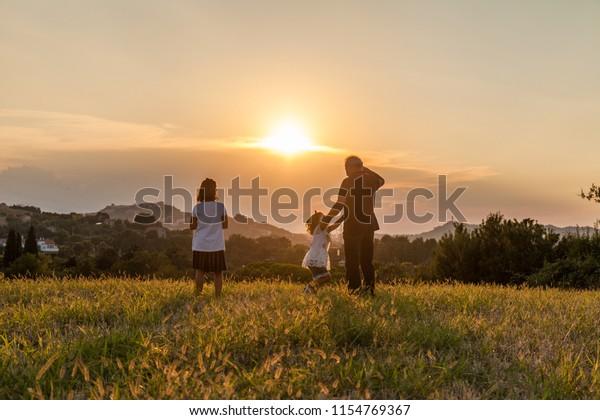 Grand-père et ses enfants, silhouette, regardent vers l'horizon au coucher du soleil. Icône famille et amour