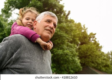 Grandfather with his granddaughter in the park.  Little girl looking at camera. Focus on grandpa.