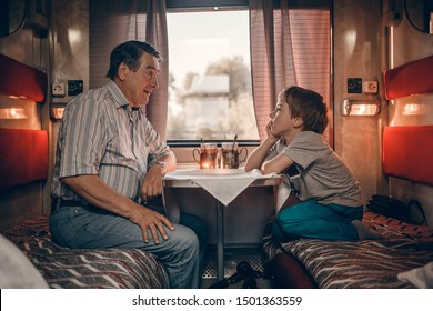 Grandfather with his grandson in the russian train drinking tea from traditional russian cups with cupholders. Image with selective focus and toning.