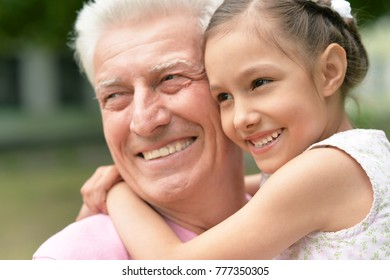 Grandfather and his little granddaughter together in park