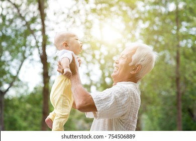 Grandfather holding baby grandchild at outdoor park, Asian family, life insurance concept.