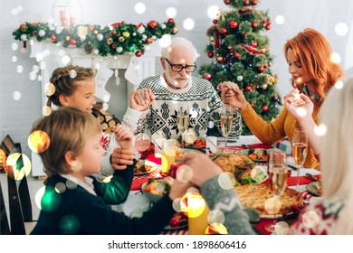grandfather holding hands during prayer with family, bokeh lights illustration