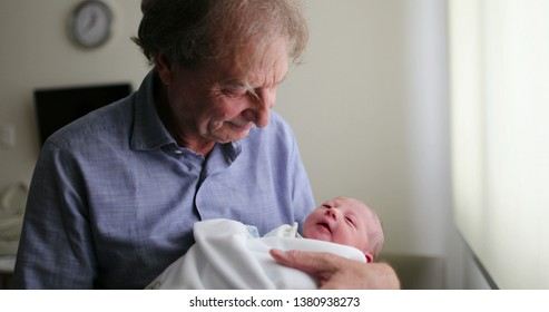 Grand-father holding newborn baby grand-son. Newborn baby infant being held by grand-father
