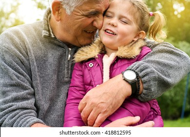 Grandfather hugging granddaughter in the park.