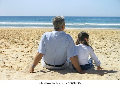 Grandfather and little girl having fun on the beach.