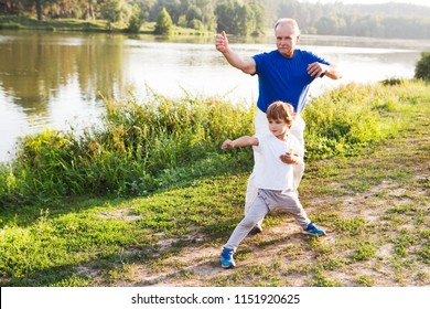 Grandfather and little grandson  practice Tai Chi Chuan outdoors.  Chinese management skill Qi's energy.