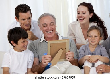 Grandfather looking at a photo with his family at home