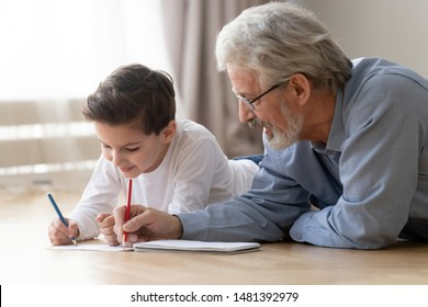 Grandfather lying on warm floor with little grandson, grandad helps to little grandkid teaches him to draw using colored pencils on paper activity at home, younger older generations connection concept