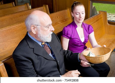 Grandfather passing offering basket to granddaughter in church pew.