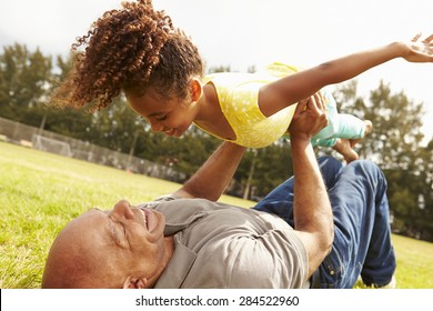 Grandfather Playing Game With Granddaughter In Park