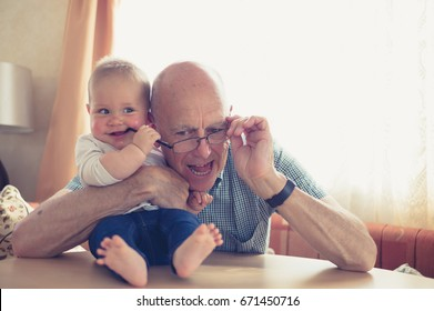 A grandfather is playing with a little baby who is grabbing his glasses