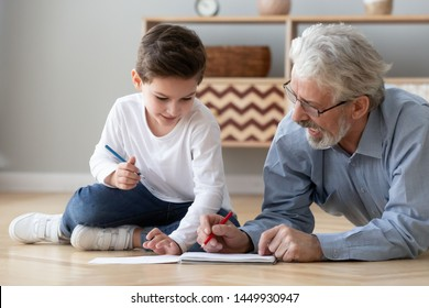 Grandfather playing with little grandson, drawing colored pencils, caring granddad and cute preschool grandchild lying on warm floor together, having fun at home, underfloor heating concept close up